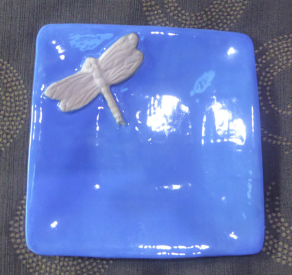 a dragonfly in a blue jewelry bowl.