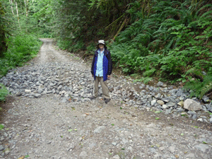 Walter Cooke with washout area of road/trail to Sunset Mine NE of Index WA